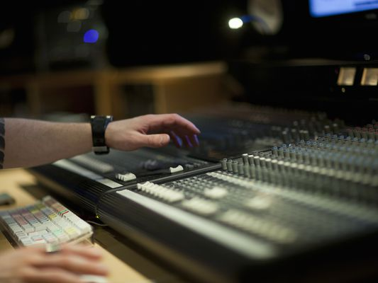 hand on mixing desk in recording studio