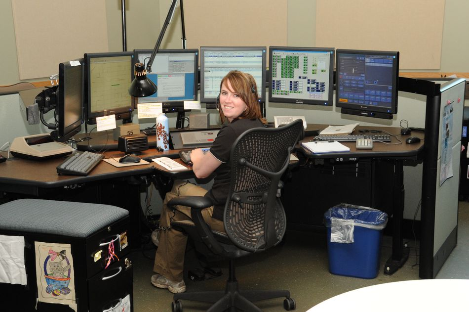 a police dispatcher in front of multiple computer monitors