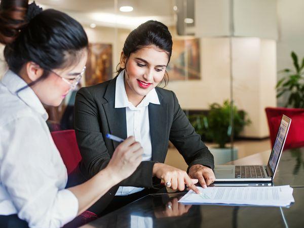A woman in business attire is showing another woman where to sign a document.