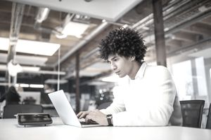 Young adult in white shirt working on laptop in his office