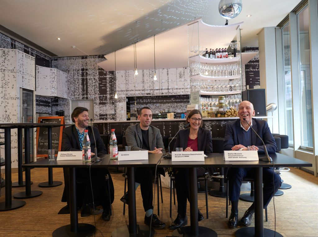 Four curators sitting at a long table to answering questions during an exhibition preview press conference
