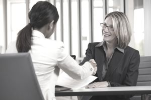 Businesswomen shaking hands across a table at a job interview.