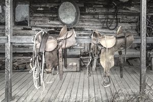 Two leather saddles hung over a wooden banister in front of a tack shop.