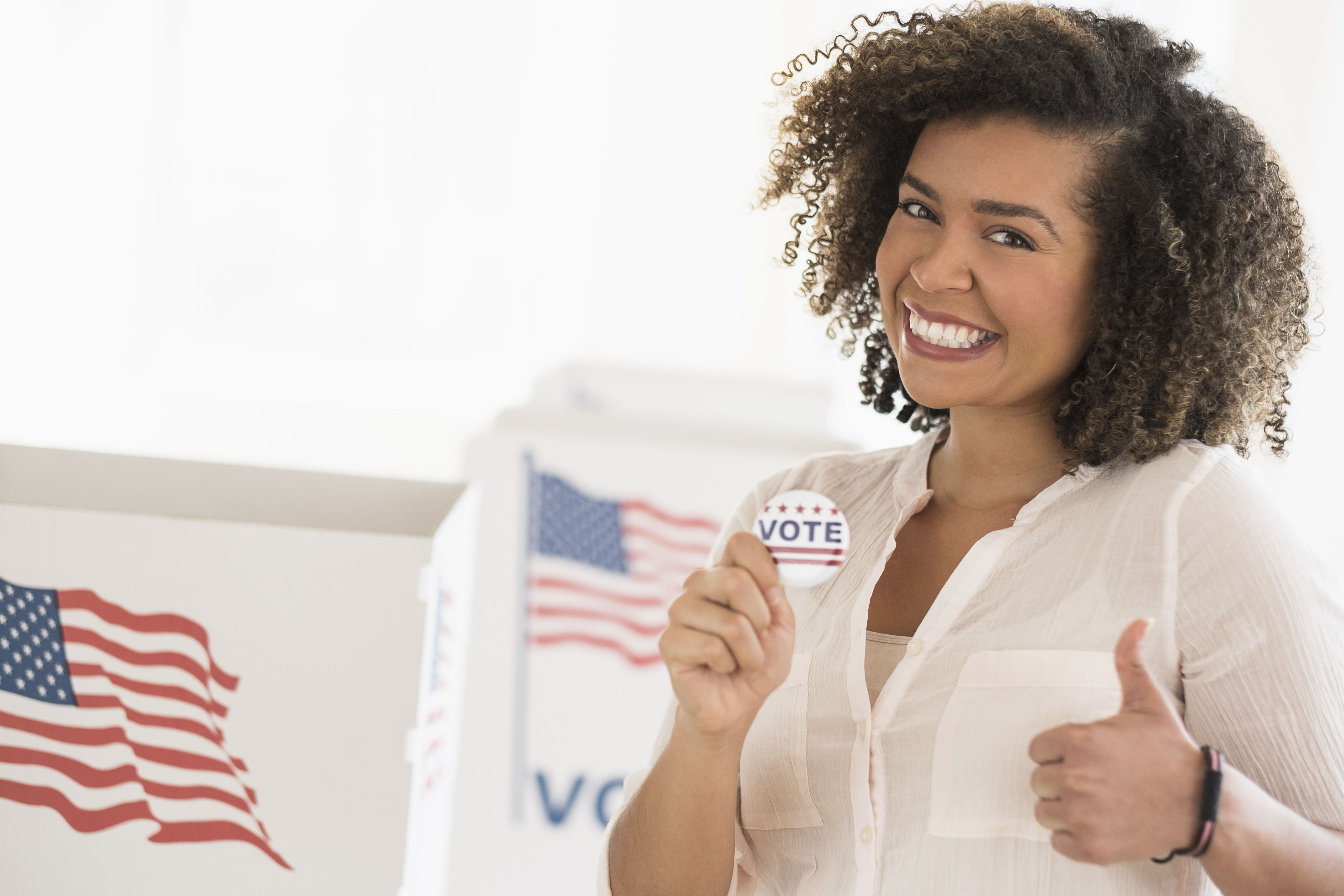 Woman holding voting badge and smiling