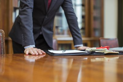 Tax lawyer with hands on table and portfolio