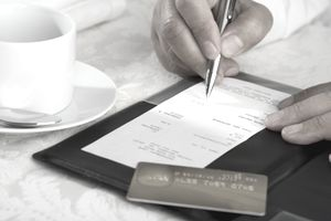Close up of man signing credit card receipt at restaurant