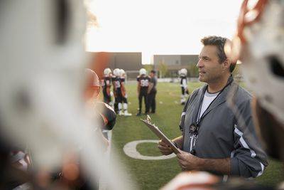 An athletic coach with a clipboard talks to his student players on the field