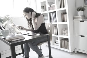 Woman sitting in front of laptop and checking her phone