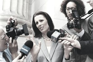 A photo of a woman surrounded by reporters