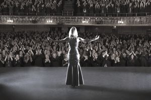 Theater performer standing with arms outstretched on stage