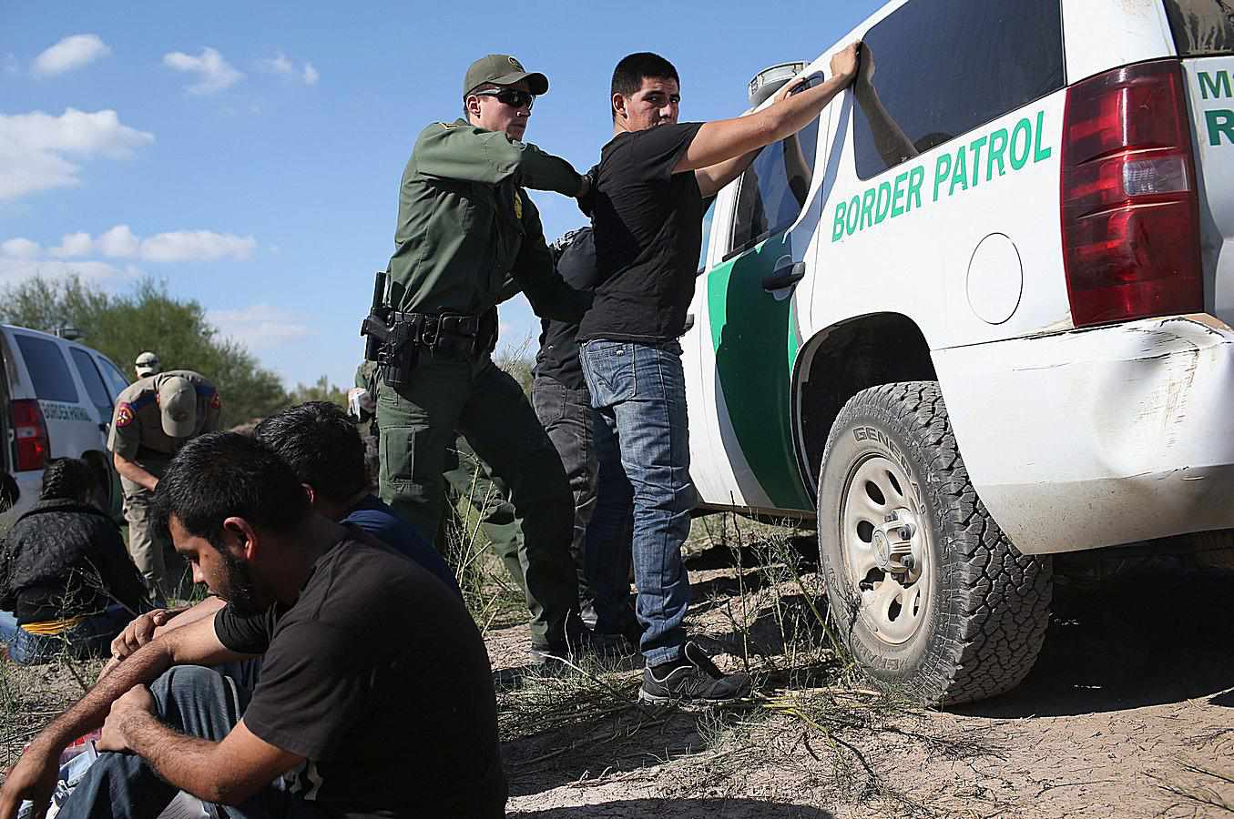 US Border Patrol agents detaining undocumented aliens on Mexican border
