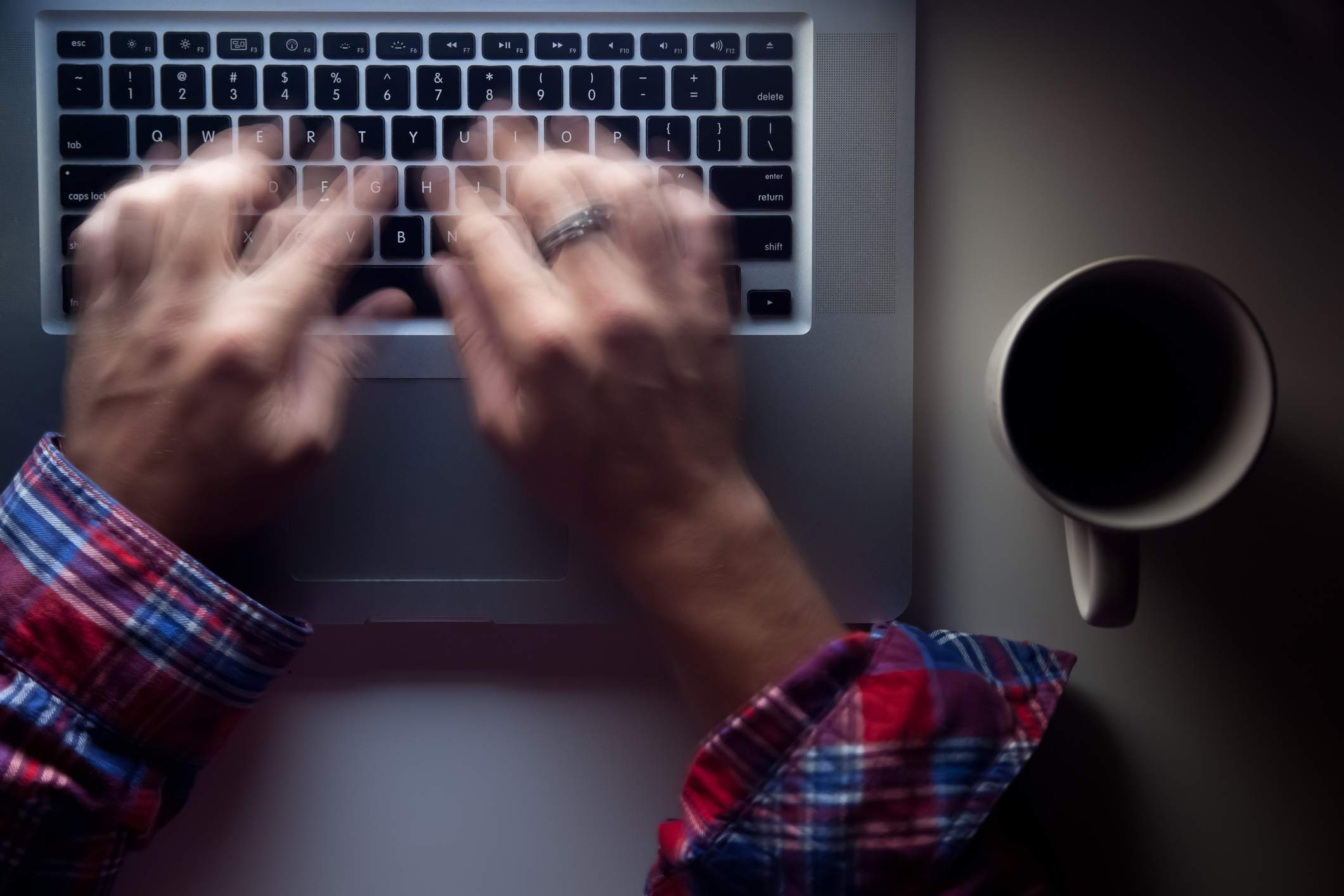 Time-lapse image of hands typing vigorously on a computer keyboard.
