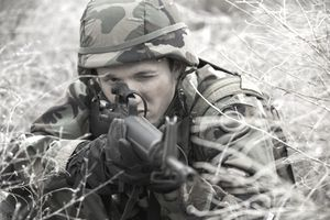 Close-up of a soldier aiming his rifle