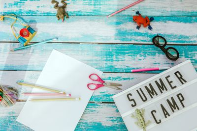 summer camp text and toys in blue background.TOP VIEw