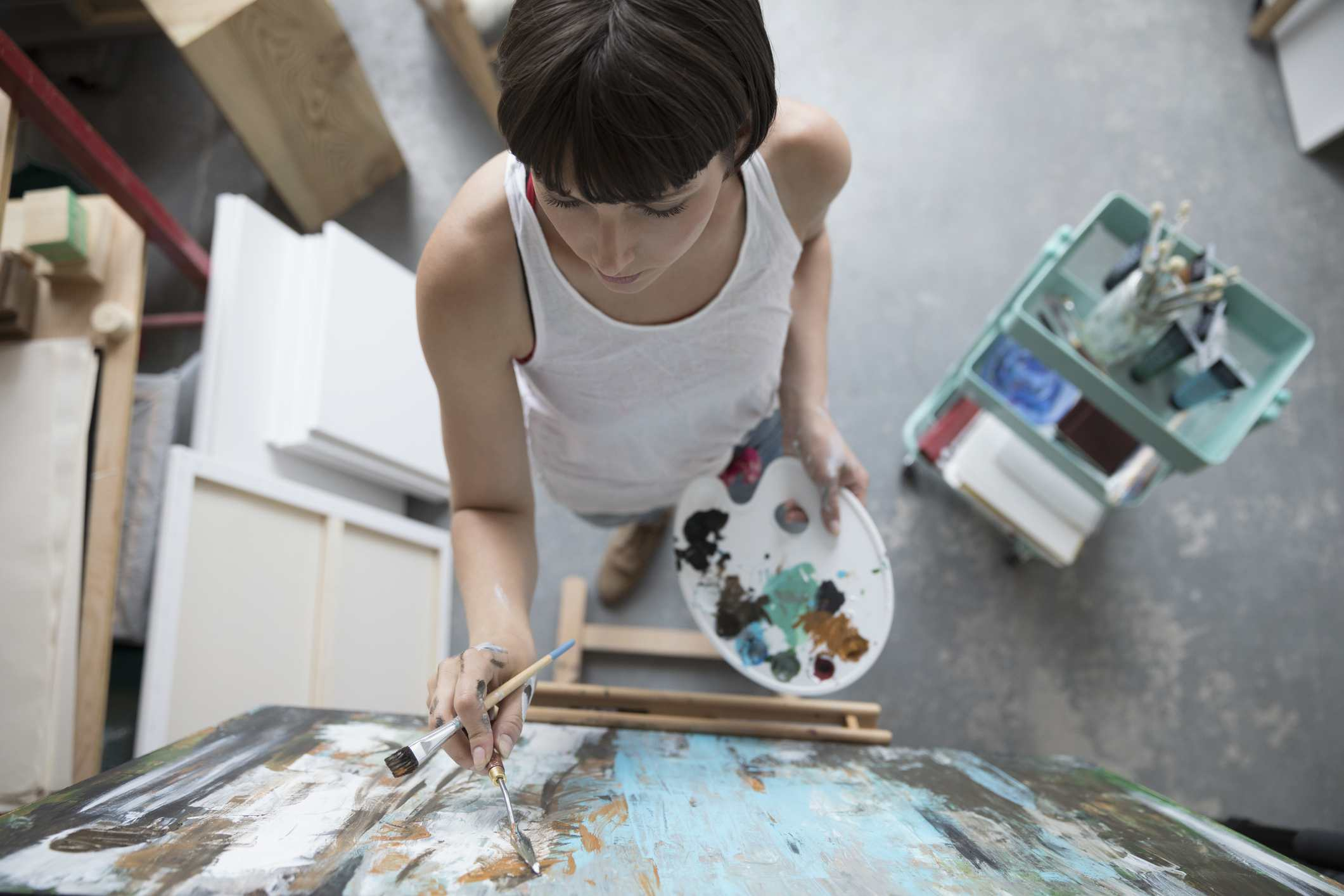 View from above female painter with palette painting at canvas in art studio