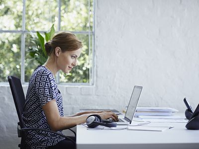woman at computer on white desk in painted white brick office