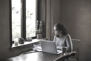 Young Woman of Mixed-ethnicity Works From Home Using Laptop Computer and Reference Book