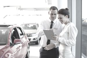 Salesman and customer using digital tablet in car dealership