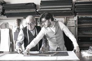 A young man working as an intern for an experienced tailor.