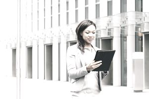 Portrait Of Successful Businesswoman Using Tablet In Urban Landscape