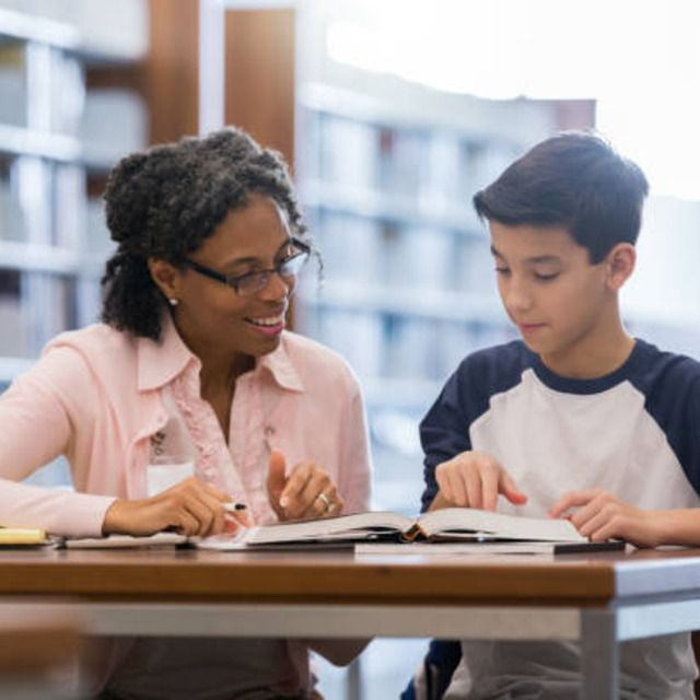 Female tutor reviewing book with tween boy in library