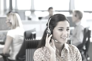 An employee wearing a headset with other employees behind her