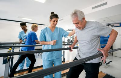 Occupational therapist helping patients walk