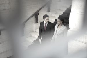 Lawyers walking past a staircase in a courthouse