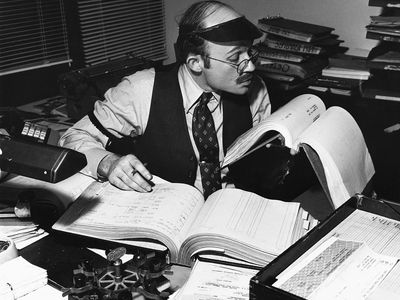 Businessman working in an office with large old fashioned budget ledgers