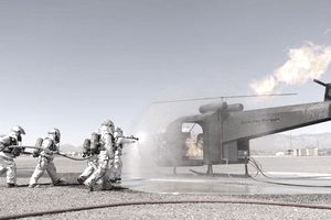 Firefighting specialists on a tarmack extinguish a fire in a helicopter during a training exercise.