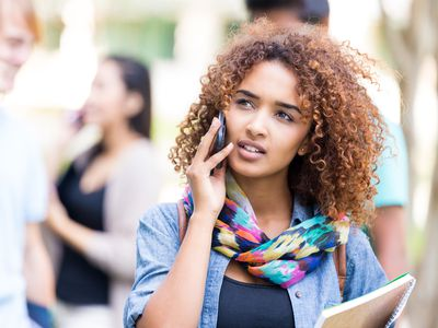 College student having conversation on cell phone outdoors