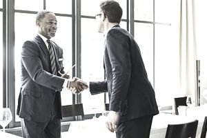 Two businessmen shaking hands at a lunch meeting