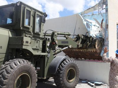 A Marine Corps engineer equipment operator directs a tractor that is tearing down a wall.