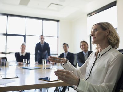 Businesswoman presenting a technical feasibility study during a meeting.