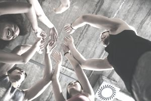Young professionals stand in a circle with arms raised in an icebreaker activity