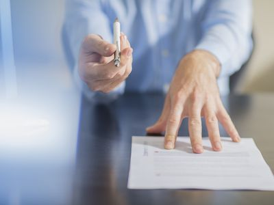 Person sitting at office desk presenting ballpen and employment contract to a prospective employee.