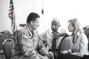 Soldier sitting in chair talking to business people