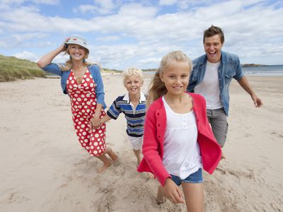 Portrait of smiling family walking on the beach when the employees uses their paid vacation time