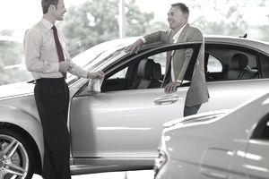 Car Salesman talking to a customer in a dealer's showroom.