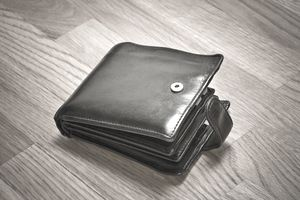 Wallet on a wooden floor, representing profit sharing.