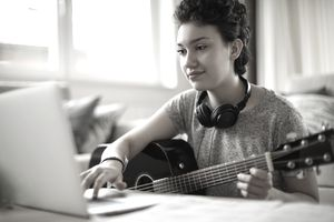 Young woman using a laptop to record herself playing guitar at home.