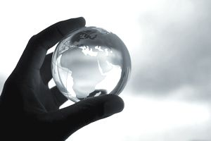 A hand holding a crystal globe