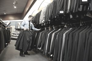 Man hanging up business suits