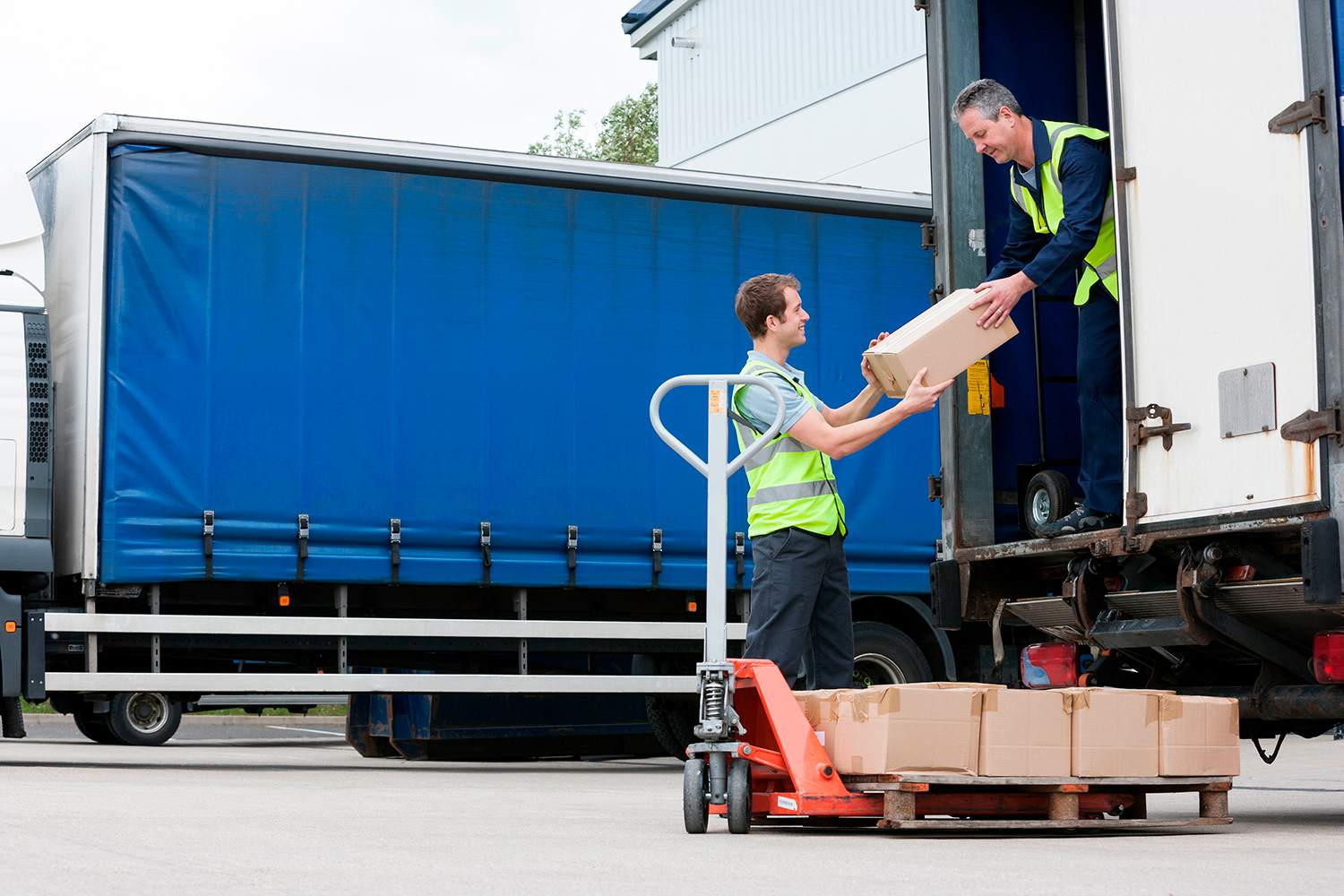 Two men unloading cardboard boxes from truck.