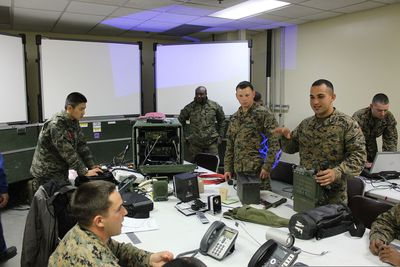 U.S. Marine Corps Lance Cpl. Steven Maldonado, right, a radio operator with Communications Company, Headquarters and Service Battalion, 3rd Marine Division, III Marine Expeditionary Force, explains the PRC-117 and its compatibility with the secure communication controller in the combined operations center during Marine Expeditionary Force Exercise.