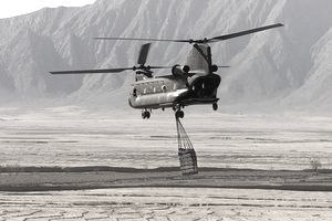 A U.S. Army CH-47 Chinook helicopter carries cargo March 15, 2002 in the rugged Shah-e-Kot mountains, about 25 kilometers (15 miles) southeast of Gardez, Afghanistan. The Chinook is flying a mission in the mountains where hundreds of American soldiers from the Army10th Mountain Division and Canadian infantry soldiers are searching for caves and enemy in rugged mountainous terrain at high altitude.