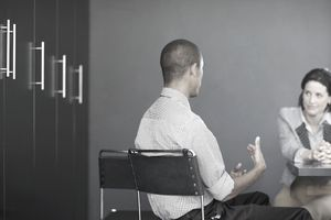 Man and woman seated in a room with a table during a job interview.