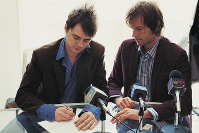 Pop Musicians Signing a Contract in a Conference Room