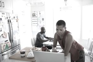 Mature woman working at laptop in morning breakfast kitchen