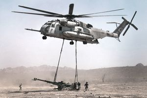 A helicopter lifts a large artillery piece from the battlefield with logistics embarkation specialists looking on.
